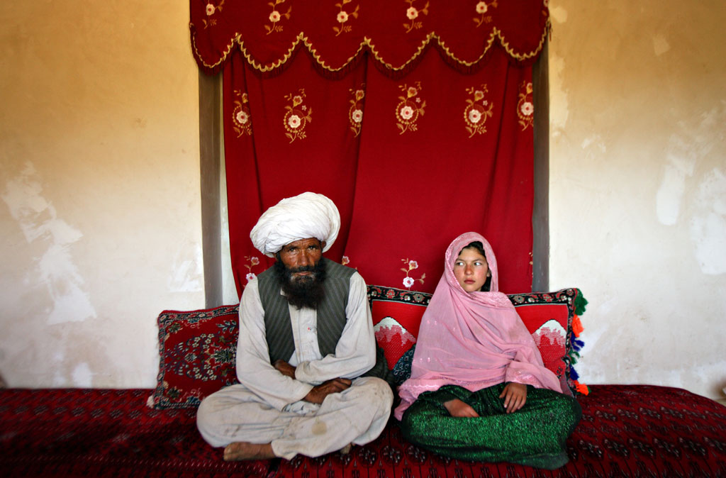 Faiz Mohammed, 40, and Ghulam Haider, 11, sit in her home prior to their wedding in the rural Damarda Village, Afghnanistan on Sept. 11, 2005.  Ghulam said she is sad to be getting engaged as she wanted to be a teacher. Her favorite class was Dari, the local language, before she was made to drop out of school. Married girls are seldom found in school, limiting their economic and social opportunities. Parents sometimes remove their daughters from school to protect them from the possibility of sexual activity outside of wedlock. It is hard to say exactly how many young marriages take place, but according to the Afghan women's ministry and women's NGOs, approximately 57 percent of Afghan girls get married before the legal age of 16. In addition, once the girl's father has agreed to the engagement, she is pulled out of school immediately. Early pregnancies also result in an increase in complications during child birth. © Stephanie Sinclair / VII
