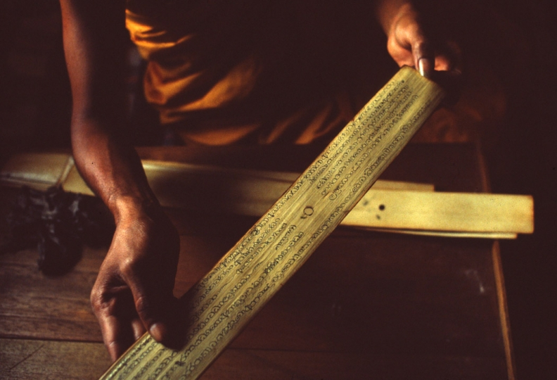 A Buddhist monk inscribes sacred ola palm leaves at the Aluvihava temple, Sri Lanka.  1982  (From the book 'Sri Lanka') © Tim Page