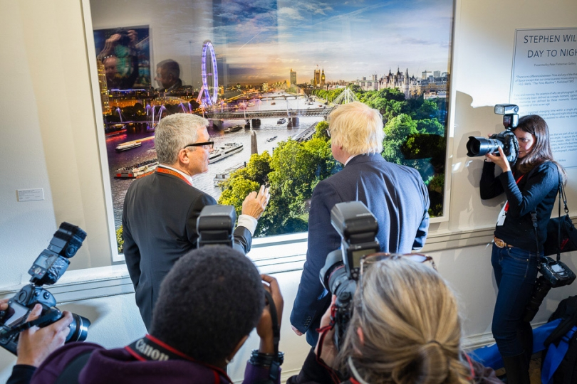 Photographer Stephen Wilkes shows his work to a visitor, London Mayor Boris Johnson © Magnus Arrevad