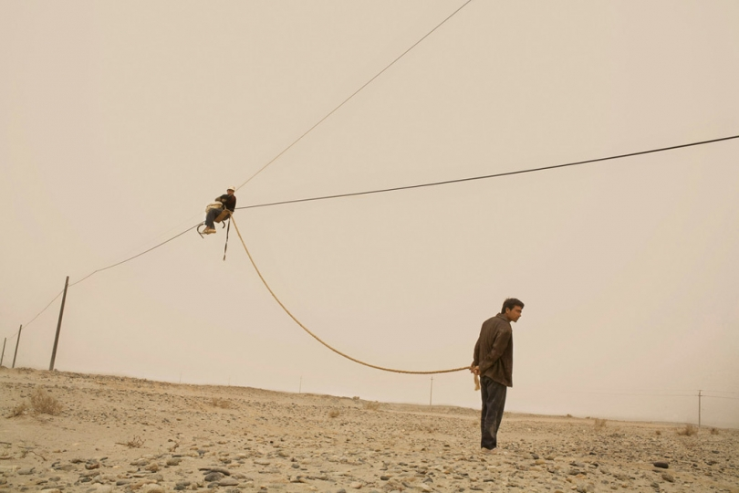 China. Xinjiang Uyghur Autonomous Region. Hotan. 2007. Uyghur laborers string electric lines across Taklamakan Desert, part of the Chinese governmentu00eds effort to develop its western frontier, a province that borders 8 countries and represents a fifth of China's territory. © Carolyn Draken