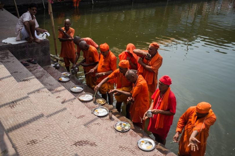 Pilgrims offering water during 'Pind Daan' ritual as the priest chants 'mantras' (prayers) at Baiterni lake. It is essential to perform the ritual at different pious sites. For us, we could cover three different locations in a day. Gaya, Bihar, India. 2015