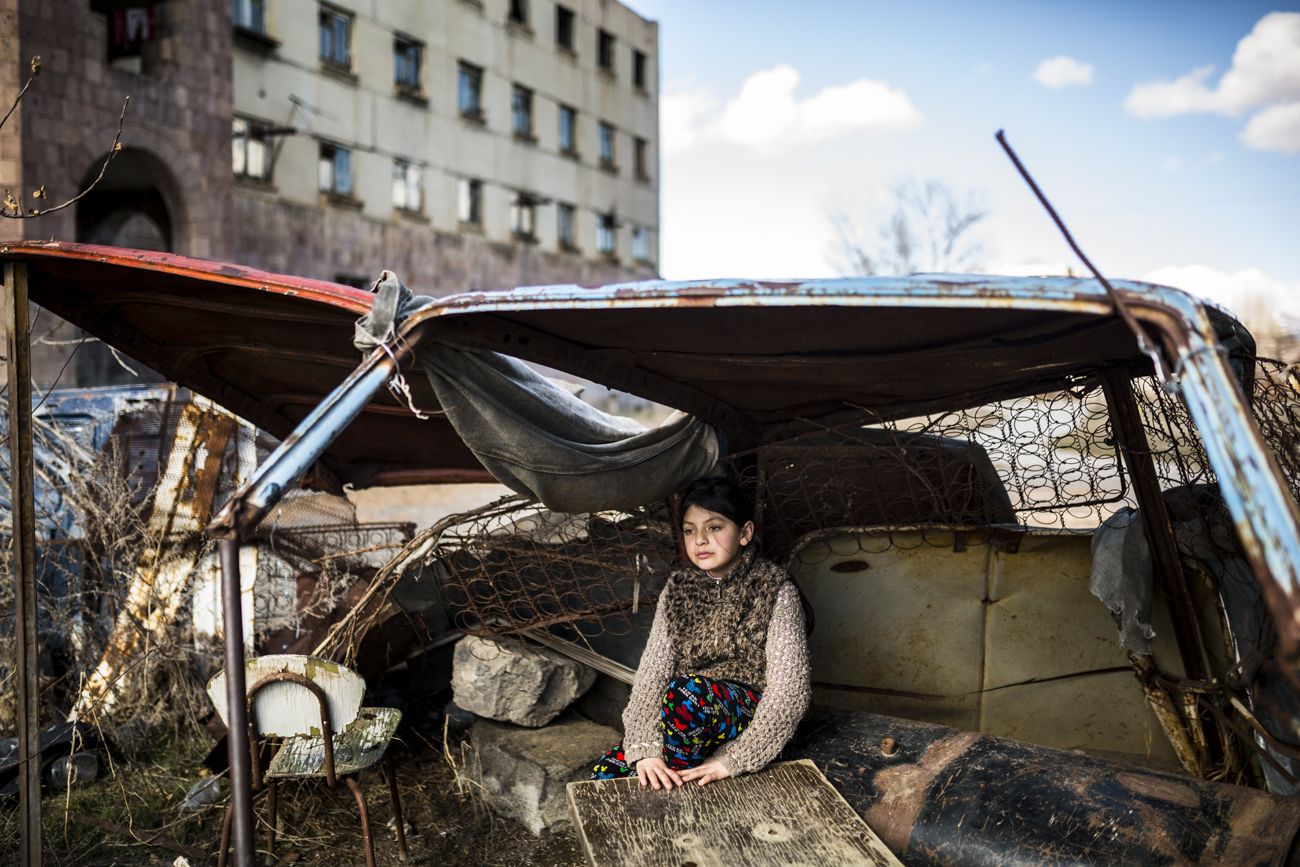 "Syuzanna (9) - one of 5 children of Lusine, sitting in a ""shelter"" made of old car rusty parts. Ten days ago Syuzanna's father committed suicide, as people say, because of debt."