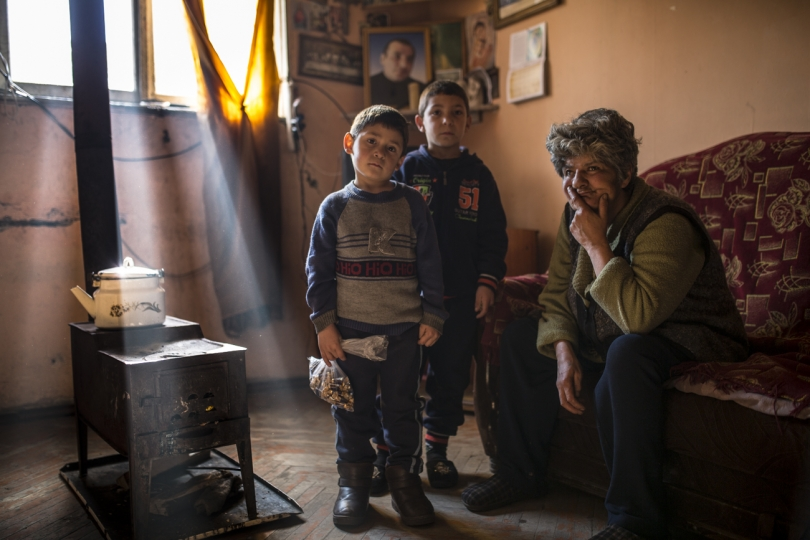 Syuzanna's brothers - Suren (5) and Levon (7) in their single room apartment, with a neighbour visiting them,10 days after their father committed suicide In Armenia, during the first 40 days after the death relatives, neighbours and other acquaintances visit the family to pay respect and support them during the most difficult days.