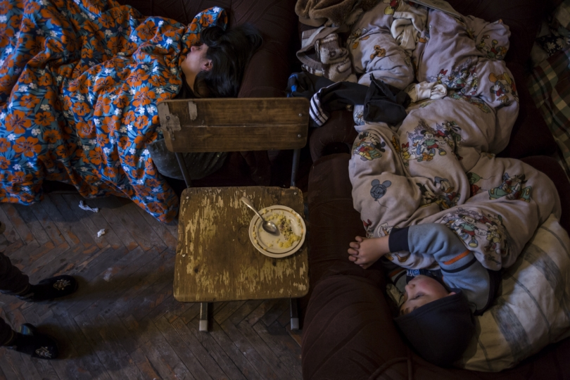 Lusine - Syuzanna's mother with her children in their tiny apartment in Gyumri, sleeping all in the only room, that serves also as kitchen and playroom for the family.