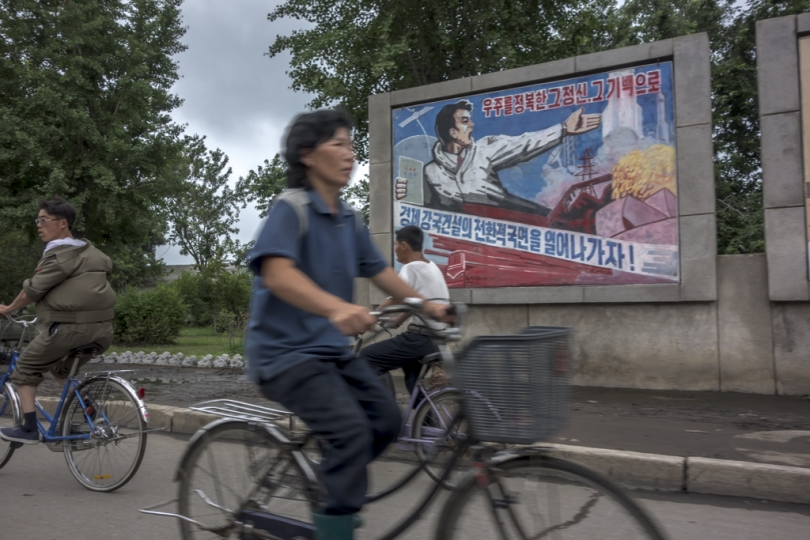 cyclists riding by a propaganda sign, Kaesong