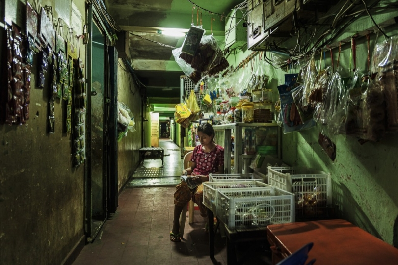 A woman sits in one of the corridors waiting to sell her goods from her shop.