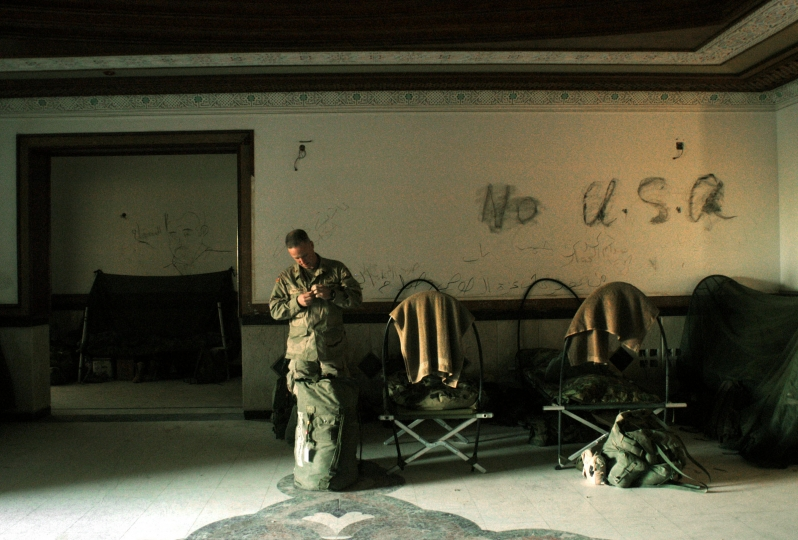 A soldier with the United States 101st Airbourne Division stands in front of Anti-American slogans drawn on the wall of the Division Main Headquarters in one of Saddam Hussain's former palaces in Mosel, Northern Iraq, May 1, 2003. The palace was Hussain's Northernmost palace in Iraq, and was his VIP palace, and now runs the entire northwest region of Iraq for the 101st Airbourne. (Credit: Lynsey Addario/ Corbis Saba)