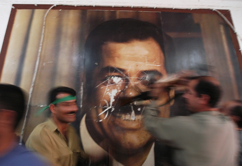 Kurdish Peshmerga soldiers deface a poster of former Iraqi leader Saddam Hussain's poster in the Kirkuk Governate building in Kirkuk hours after it fell from Iraq Central Government rule, April 10, 2003. Roughly twenty days after the start of the US-lead war on the regime of former Iraq leader Saddam Hussain, cities are falling out of his control, and locals celebrate and destroy statues and symbols of Hussains power. (Credit: Lynsey Addario/ Corbis)