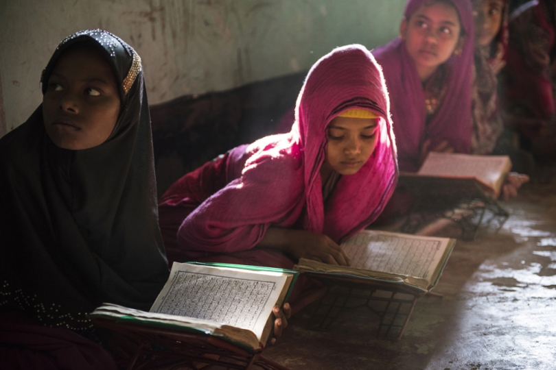 Sitara, 8, left, and Shahana, 10, right, read the Koran at a madrassa in a mosque in Shamlapur, a Rohingya settlement, outside of Cox's bazaar, Bangladesh, January 2016. While there are very few opportunities for Rohingya children to go to school on account of a lack of teachers, books, and means, most children do study the Koran at the local madrassa with the Imam of the community. The Rohingya are systematically marginalized, and forced into formal and makeshift camps across Bangladesh and Myanmar.