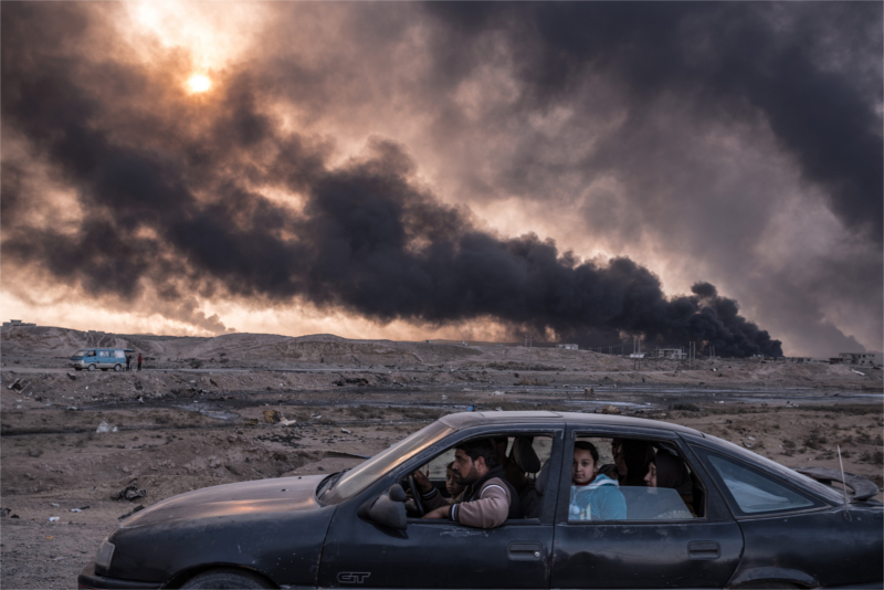 A family fled the fighting in Mosul past oil fields set alight by Islamic State militants near Qayyara, Iraq in November. Seeking to escape the bloodshed, more civilians than ever took the risk of evacuation that month, hoping to find help if they could make it past the militants' gun range. By December, up to one million people were trapped inside the city, running low on food and drinking water and facing the worsening cruelty of Islamic State fighters.