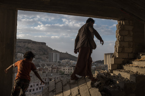 Alex Kay Potter, Yemeni brothers climb the broken stairs of an apartment building damaged by airstrikes in the Faj Attan © Alex Kay Potter