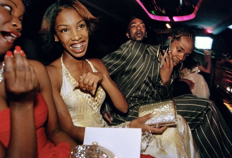 "Crenshaw High School girls selected by a magazine to receive ""Oscar treatment"" for a prom photo shoot take a limo to the event with their dates, Culver City, California, 2001. © Lauren Greenfield"