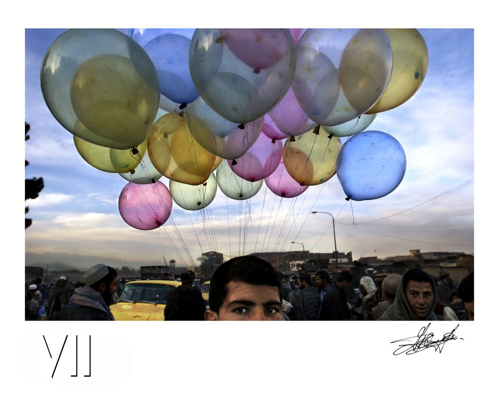 John Stanmeyer, Colorful balloons with a traveling vendor in sharp contrast with the dust and ruined city of Kabul on November 18, 2001. © VII Agency