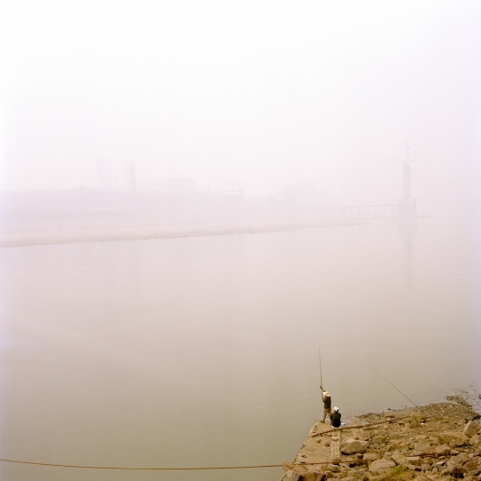 Tim Franco, Fishermen in Chongquing, Local people fishing on the Jialing river downtown Chongqing. The polustion dust is so strong that we cant see any side of the city © EPAU