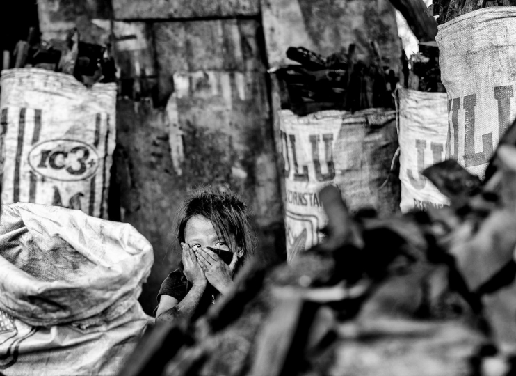 A small girl covers her face as she takes a break from packaging large bags of charcoal, Manila, Philippines, 25 December, 2017. Despite being banned in many districts, illegal charcoal harvesting continues secretly within many of Manila's outer suburban slums. Just a few kilometres from Manila's city centre the poorest of the slum families' risk their lives to make just a few pesos in the illegal charcoal making business in appalling conditions. © Ted McDonnell