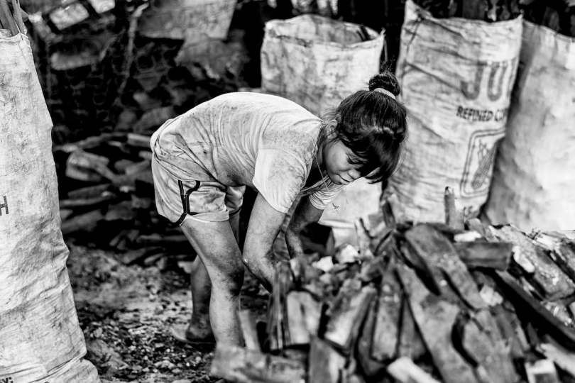 A young girl packs a bag of charcoal for just a few cents in Manila's slums, Manila, Philippines, 25 December, 2017. Despite being banned in many districts, illegal charcoal harvesting continues secretly within many of Manila's outer suburban slums. Just a few kilometres from Manila's city centre the poorest of the slum families' risk their lives to make just a few pesos in the illegal charcoal making business in appalling conditions. © Ted McDonnell