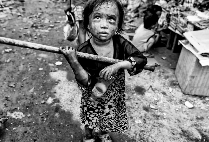 A small child, her face covered with charcoal carries a stick she uses to carry small bags of charcoal in Manila's slums, Manila, Philippines, 25 December, 2017. Despite being banned in many districts, illegal charcoal harvesting continues secretly within many of Manila's outer suburban slums. Just a few kilometres from Manila's city centre the poorest of the slum families' risk their lives to make just a few pesos in the illegal charcoal making business in appalling conditions. © Ted McDonnell