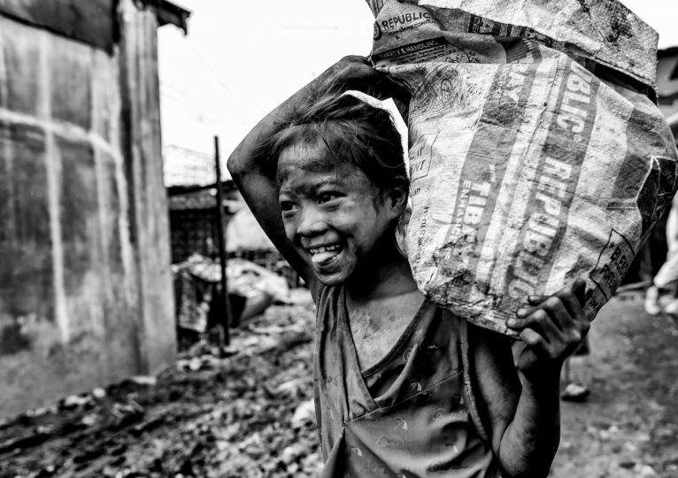 A girl carries a heavy bag of charcoal through one of Manila's charcoal producing slums, Manila, Philippines, 25 December, 2017. Despite being banned in many districts, illegal charcoal harvesting continues secretly within many of Manila's outer suburban slums. Just a few kilometres from Manila's city centre the poorest of the slum families' risk their lives to make just a few pesos in the illegal charcoal making business in appalling conditions. © Ted McDonnell
