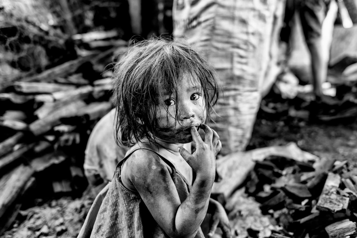 A small girl her face covered with black soot  watches her mother pack charcoal in one of Manila's charcoal producing slums, Manila, Philippines, 25 December, 2017.  Despite being banned in many districts, illegal charcoal harvesting continues secretly within many of Manila's outer suburban slums. Just a few kilometres from Manila's city centre the poorest of the slum families' risk their lives to make just a few pesos in the illegal charcoal making business in appalling conditions. © Ted McDonnell