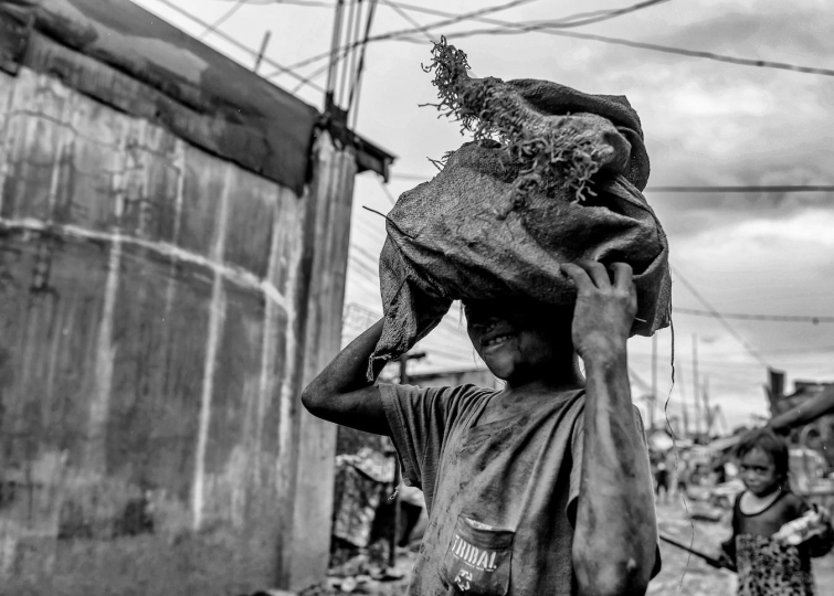 A young girl's head is partially covered by a bag of charcoal as she carries it through a Manila slum to a buyer, Manila, Philippines, 25 December, 2017. Despite being banned in many districts, illegal charcoal harvesting continues secretly within many of Manila's outer suburban slums. Just a few kilometres from Manila's city centre the poorest of the slum families' risk their lives to make just a few pesos in the illegal charcoal making business in appalling conditions. © Ted McDonnell