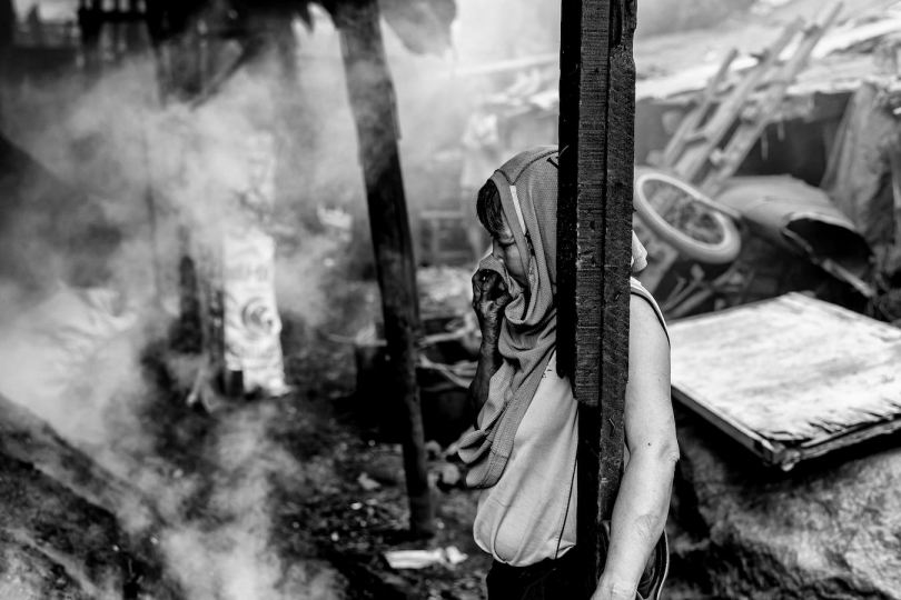 A charcoal producer covers her face from the acrid smoke produced by the kiln, Manila, Philippines, 25 December, 2017. Despite being banned in many districts, illegal charcoal harvesting continues secretly within many of Manila's outer suburban slums. Just a few kilometres from Manila's city centre the poorest of the slum families' risk their lives to make just a few pesos in the illegal charcoal making business in appalling conditions. © Ted McDonnell