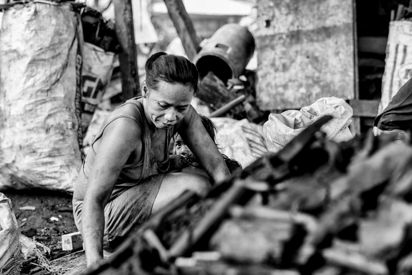A woman with child packs the charcoal for just a few cents a bag, Manila, Philippines, 25 December, 2017. Despite being banned in many districts, illegal charcoal harvesting continues secretly within many of Manila's outer suburban slums. Just a few kilometres from Manila's city centre the poorest of the slum families' risk their lives to make just a few pesos in the illegal charcoal making business in appalling conditions. © Ted McDonnell