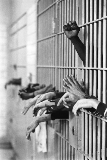 Manhattan, New York City, NY. September 28th, 1972. Hands from behind the bars at Toms Prison. Standing on Center Street at Leonard Street, and was built in 1840 with granite from the old Bridewell Prison in City Hall. © Jean-Pierre Laffont