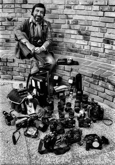 August 24th 1979, Paris. Jean Pierre Laffont posing with his cameras for Nikon article. Courtesy of Diego Goldberg. © Jean-Pierre Laffont