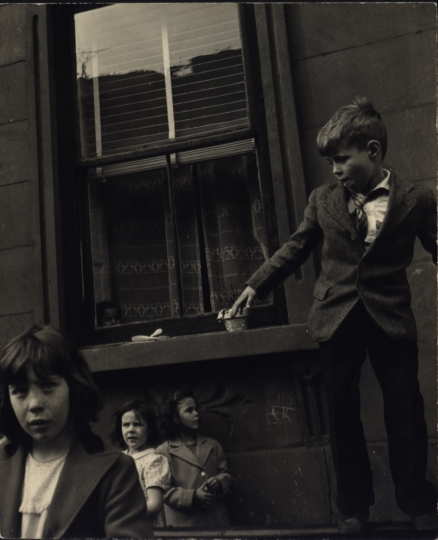 Children standing on the street near an open window, New York City, ca. 1945 © Sandra Weiner