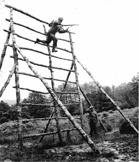 A Commando instructor follows a 1st Battalion rangers as they leap from a 20-foot high wooden structure into a mud hole, one of three obstacles on the Tarzan Course at the Commando training depot in Scotland. © Phil Stern Archives