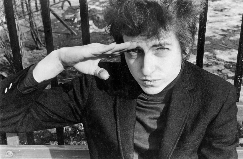 Bob Dylan, sitting on a bench in Christopher Park (across the street from the offices of the Village Voice since 1960), either salutes or shields his eyes from the sun, January 22, 1965 Vintage gelatin silver print, printed ca. 1965 - Copyright Fred W. McDarrah, Courtesy Steven Kasher Gallery, New York