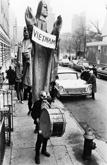 In one of the first protests in New York City against the Vietnam War, masked members of the Bread and Puppet Theater, led by artist, writer, and director Peter Schumann, march down Thompson St. from Washington Square, March 15, 1965 Vintage gelatin silver print, printed ca. 1965 - Copyright Fred W. McDarrah, Courtesy Steven Kasher Gallery, New York