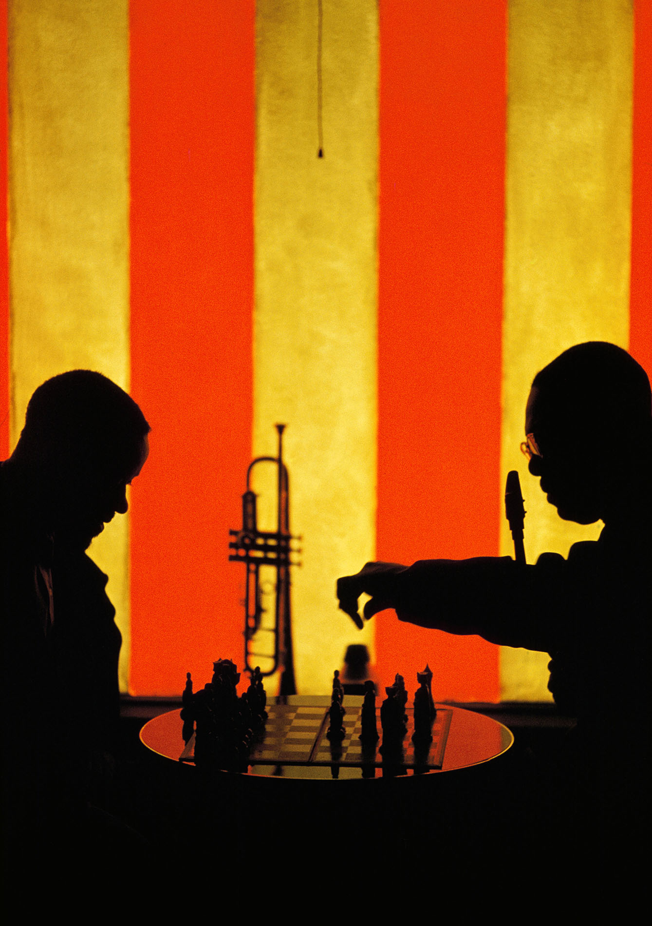 USA. San Francisco. 1960. Earl Bostic and his trumpet player playing chess during a break at the Blackhawk. That is the sun coming through the red and white striped window. Pretty jazzy eh, Dad? This is the end of Take One. No extra charge for listening to bad poetry.  © Burt Glinn / Magnum Photos