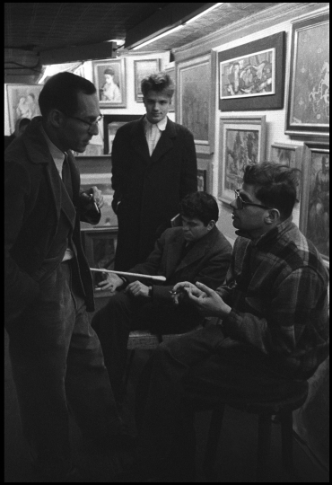 USA. New York City. 1957. Writer Allen GINSBERG and Barney ROSSET talk in an art gallery. Gregory CORSO and Peter ORLOVSKY are in the background. © Burt Glinn / Magnum Photos