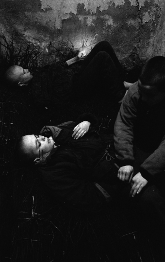 Street kids Yura, Dima and Slava at the basement where they spend nights. Dima, who has cigarettes, is sleeping already, but Yura and Slava want to have a smoke. Ukraine, Kiev, 1996 © Alexander Glyadyelov