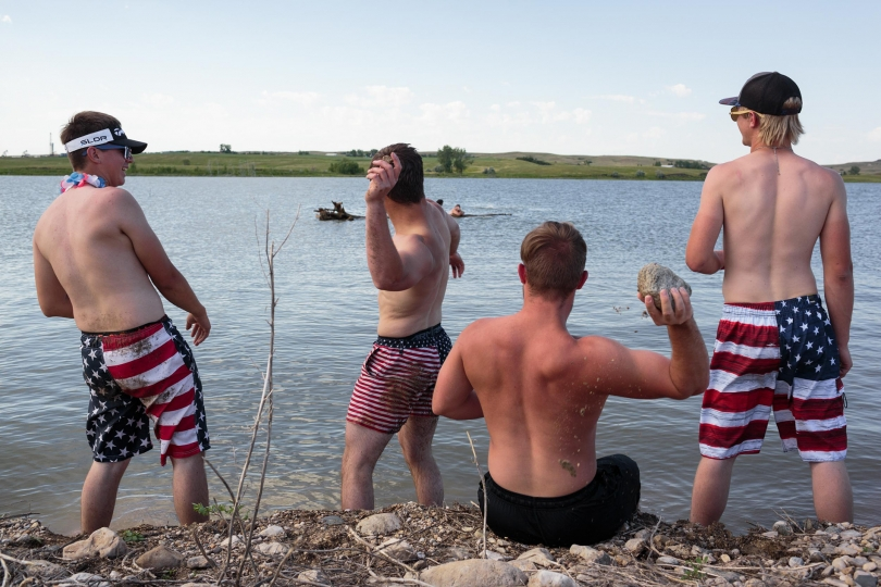 "Jamison, Jade, Gregory and Nick, throw rocks at their friends swimming in the distance, celebrating the 4th of July holiday on the Fort Berthold Reservation, 3 July 2017, North Dakota. The group is saying goodbye to one of their friends, Logan, who leaves in two days for boot camp for the Marines. His grandpa inspired him, and he didn't want to work on the oil fields. - ""Beckon Us From Home"" © Sarah Blesener – Courtesy W. Eugene Smith Memorial Fund"