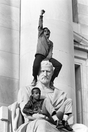 May 1, 1970 - New Haven, Connecticut, USA: Boy gives raised fist salute as he and a friend sit on a statue in front of the New Haven County Courthouse during a demonstration of 15,000 people during the Bobby Seale / Ericka Huggins trial. Bobby Seale, Chairman of the Black Panther Party is on trial along with Ericka Huggins for murder. Both are acquitted. (Stephen Shames/courtesy Stephen Kasher Gallery)