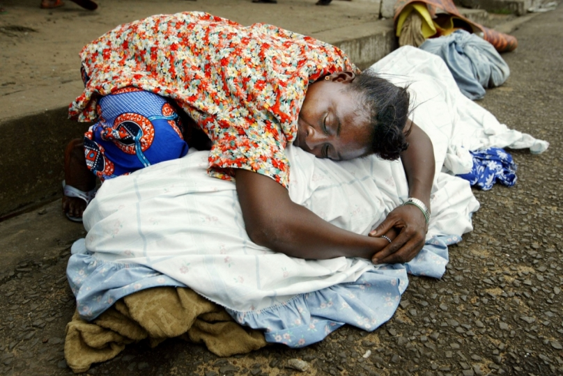 Monrovia, Liberia - July 26, 2003: A woman grieves over the body of a relative outside a church in Monrovia, Liberia. Sporadic shelling continued overnight in Monrovia, hitting a church that houses dozens of families and killing at least three. © Chris Hondros / Getty Images