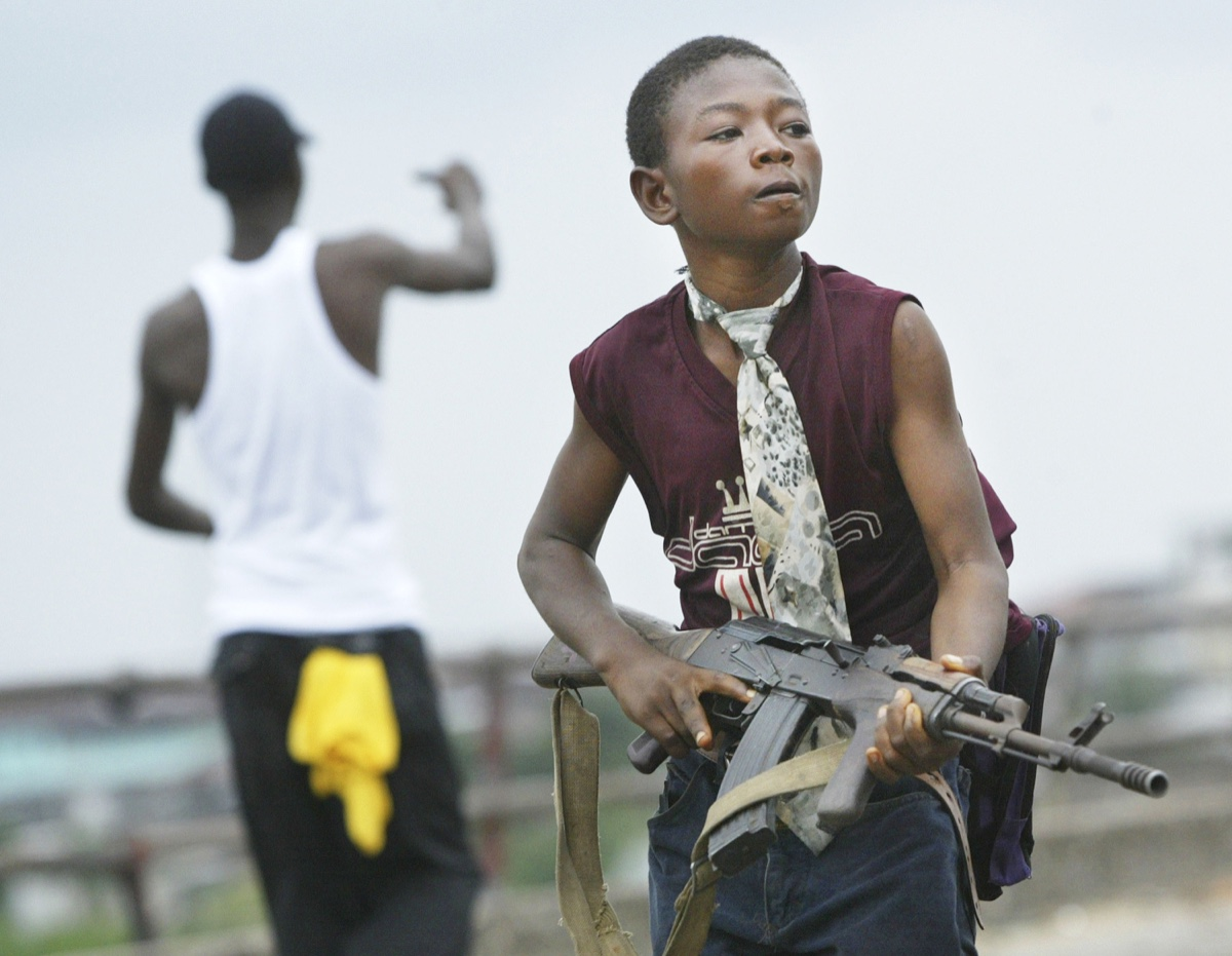 Monrovia, Liberia, July 30, 2003 - A child Liberian militia soldier loyal to the government walks away from firing while another taunts them on July 30, 2003 in Monrovia, Liberia. Sporadic clashes continue between government forces and rebel fighters in the fight for control of Monrovia. © Chris Hondros / Getty Images