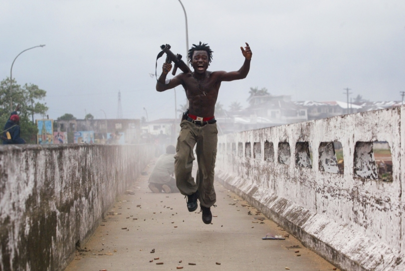 July 20, 2003: Joseph Duo, a Liberian militia commander loyal to the government, exults after firing a rocket-propelled grenade at rebel forces at a key strategic bridge in Monrovia © Chris Hondros / Getty Images
