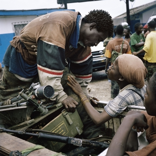 Liberia. Monrovia. June 25th, 2003. A member of the AA (Anti-Aircraft) brigade exchanges a brief tender word with his girlfriend during a heavy fighting in the capital Monrovia. ©Tim Hetherington / Magnum Photos