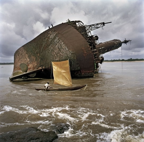 Liberia. Greenville. September 2005. A fisherman passes the wreck of an old ship off port of Greenville. Liberia is scattered with boat wrecks owing to the 14 year civil war. ©Tim Hetherington / Magnum Photos