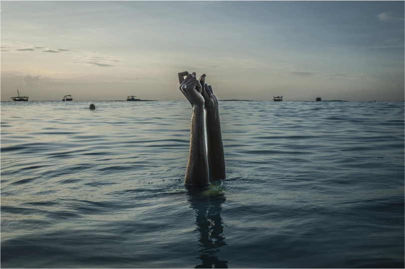 Anna Boyiazis, Chema snaps her fingers as she disappears underwater on Wednesday, December 28, 2016 in Nungwi, Zanzibar - Courtesy the artist and the Aaron Siskind Foundation