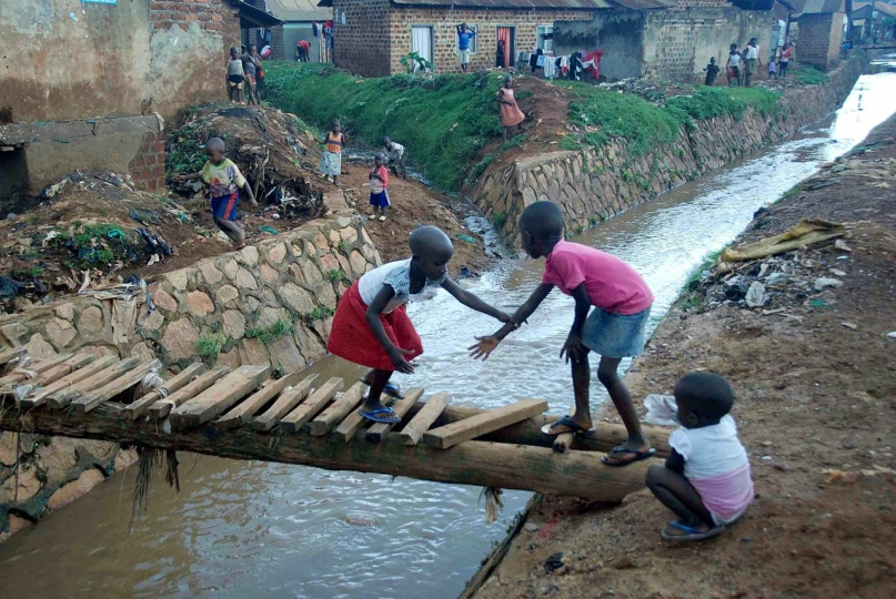 Moses Lemisa 1st Place, Urban Risky Children use a makeshift bridge to cross a water channel in Kikoni, Makerere III, in Kampala. Many neighbourhoods in the capital city are constructed informally, and open drainage is widely used to manage waste as well as the heavy water flows that come during rainy season, but these wide channels brimming with contaminated outflows provide hazards for residents as well as breeding grounds for disease.