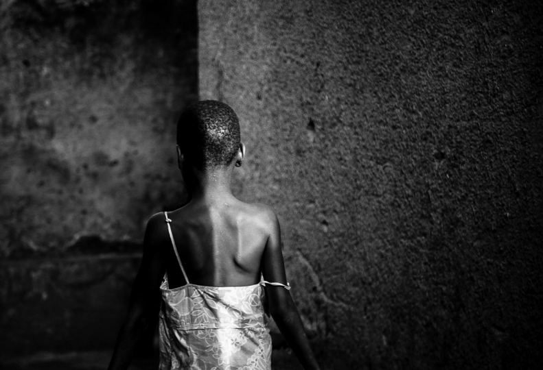 Julius Ssekidde 3rd Place, People Light is Knowledge Light is the sun and the avenger of evil forces and darkness. Light is knowledge, purity and morality. A young girl passes between intersecting walls in the evening hours in Kibuye, a Kampala suburb.