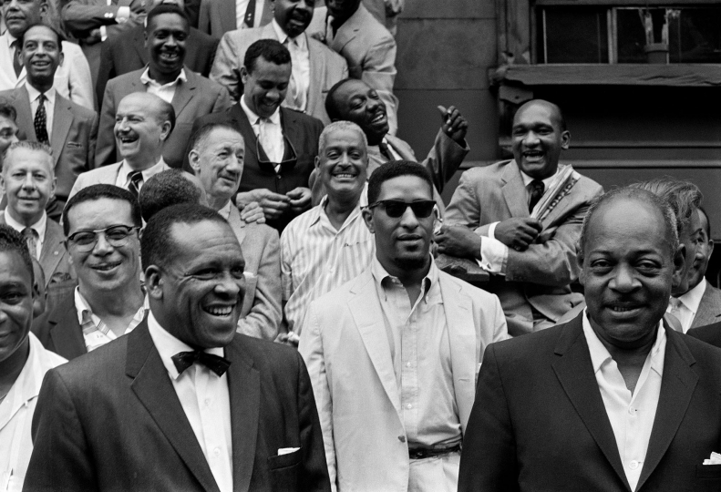 Front row, from left: Bill Crump, Stuff Smith, Sonny Rollins, Coleman Hawkins. At their back you can spot George Wettling, Bud Freeman, Pee Wee Russell, Buster Bailey, Oscar Pettiford. Behind them, Sonny Greer, Jimmy Jones, Charles Mingus, Osie Johnson - Art Kane: Harlem 1958: The 60th Anniversary Edition © Art Kane