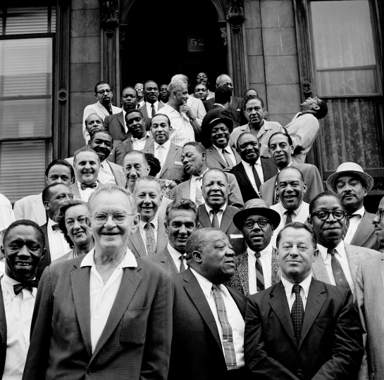 Front row, from left: Stuff Smith, Marian McPartland, Miff Mole, Gene Krupa, Jimmy Rushing, Roy Eldridge, Max Kaminsky, Hilton Jefferson. The one laughing on the right, up the stairs, is Dizzy Gillespie - Art Kane: Harlem 1958: The 60th Anniversary Edition © Art Kane