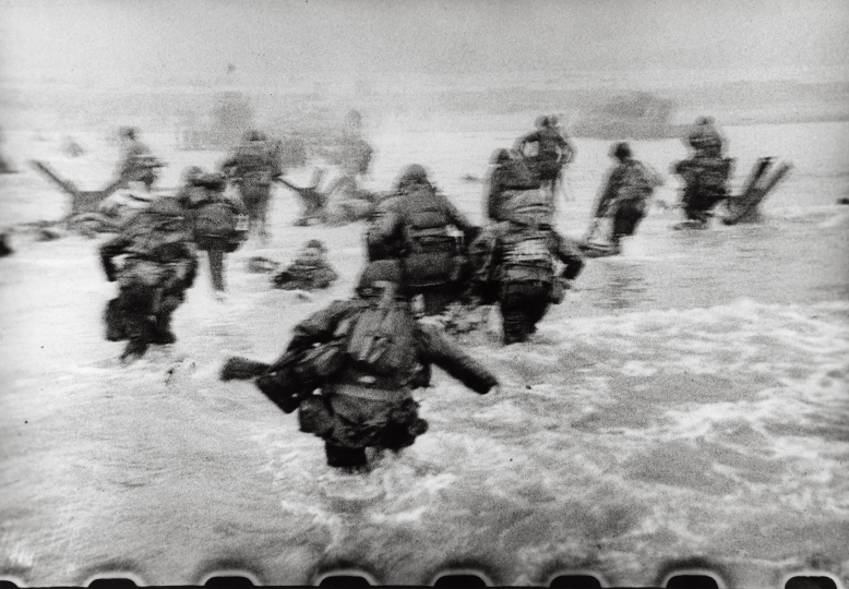 Robert Capa - Courtesy International Center of Photography/Magnum Photos American soldiers landing on Omaha Beach, D-Day, Normandy, France. June 6, 1944.