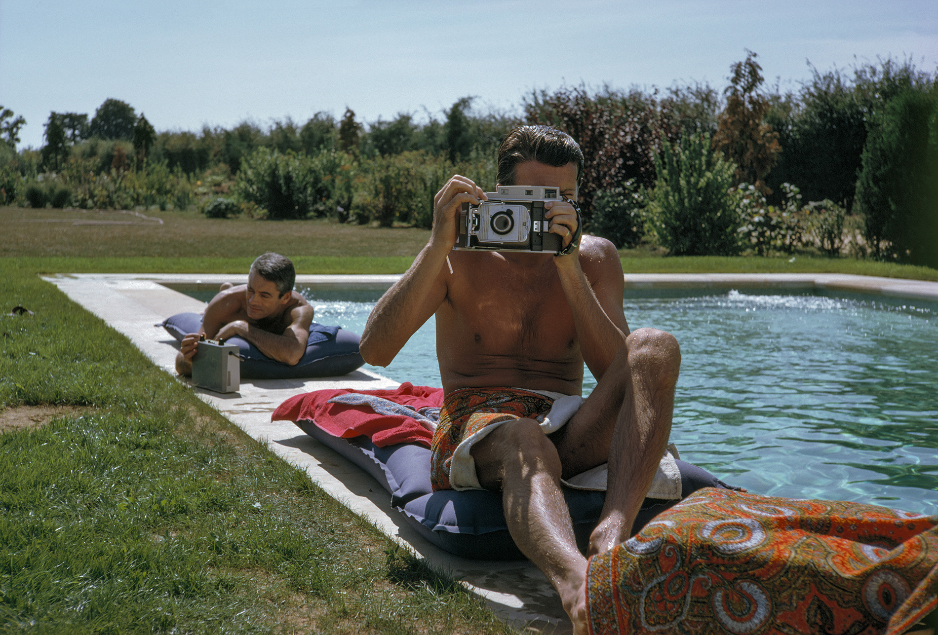 Givenchy takes a photograph by the Pool, South of Paris, France, 1961 © TONY VACCARO - COURTESY MONROE GALLERY OF PHOTOGRAPHY