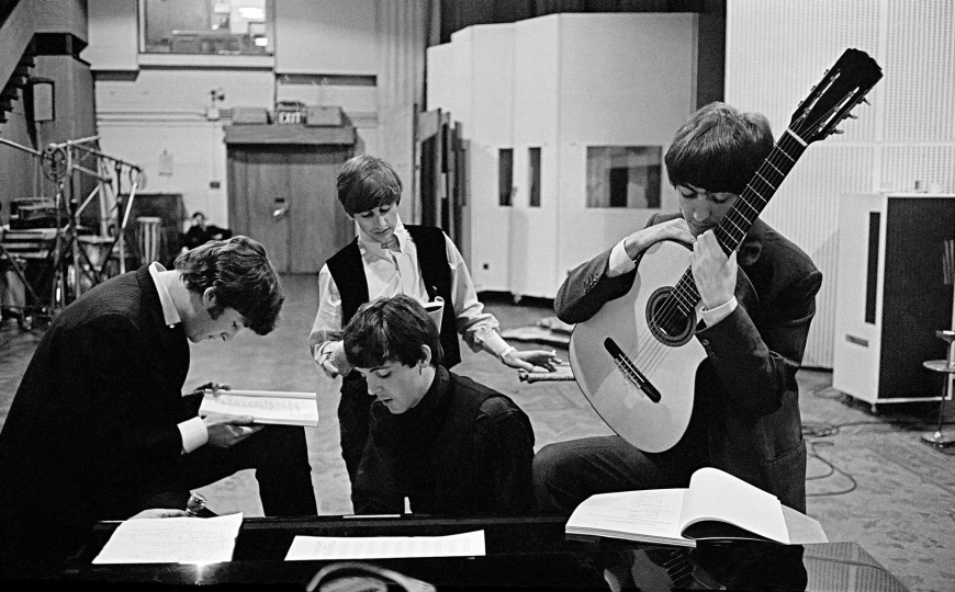David Hurn - Courtesy Magnum Photos. G.B. ENGLAND. LONDON. The Beatles in EMI Studios, later renamed Abbey Road Studios, where many of their most famous records were made, examining the script of the film 'A Hard Days Night'. 1964.